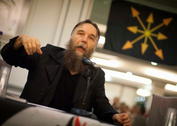 Dugin giving a talk before a chaos star banner.
